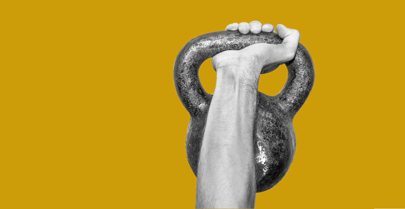 Hand lifting a kettlebell on yellow background